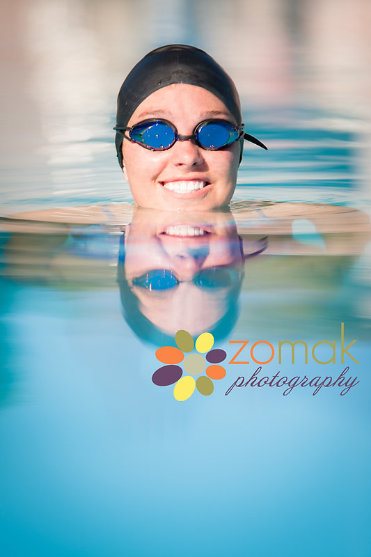 swimmer's smiling face reflects in the pool water.