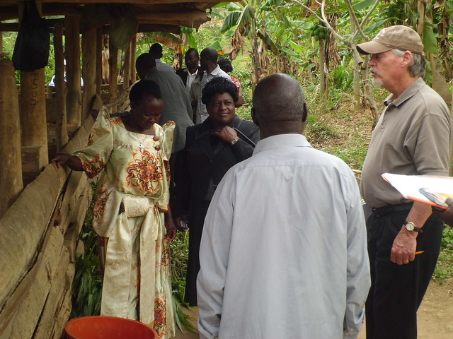 Doyle Baker (with cap) shares a moment with Mr. & Mrs Luswata at their pig farm, and Eve Luvumu (NAADS)