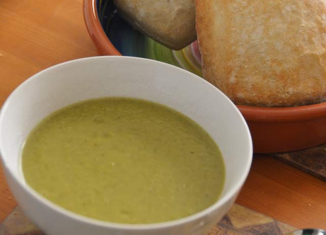 bowl of green soup with crusty rolls in background
