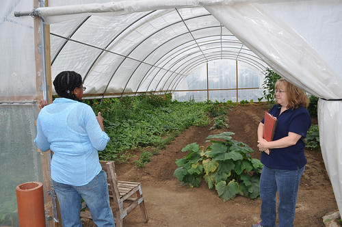 Hallie Robinson, left, and NRCS District Conservationist Lori Bataller, survey the rapid growth of produce in the high tunnel. NRCS photo.