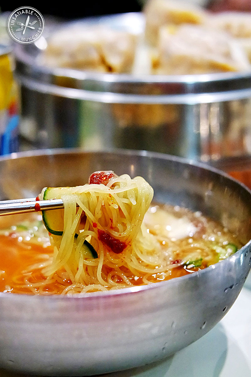 Chewy wheat noodles are served in a cold tangy broth, accompanied by a chilli paste, slivers of cucumber and pickled radish.