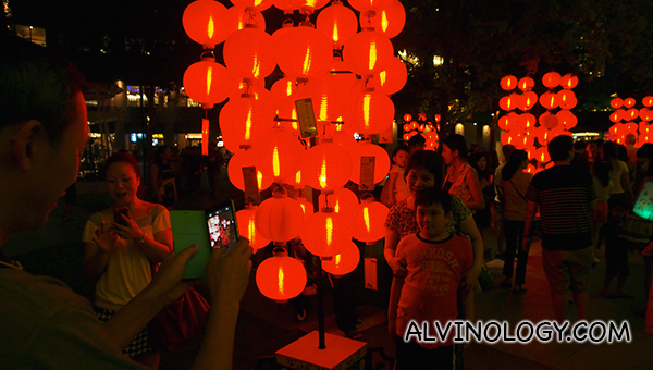A family taking photos beside the outdoor lantern displays at esplanade