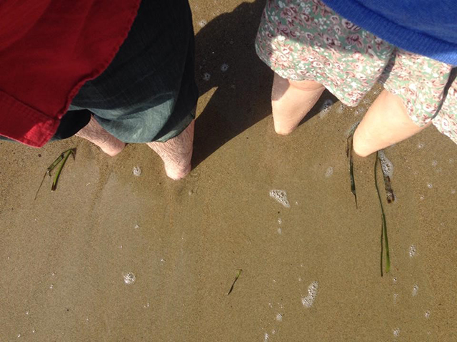 feet sunk in the sand at the beach