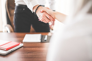 business man and woman handshake in work office | by perzonseo
