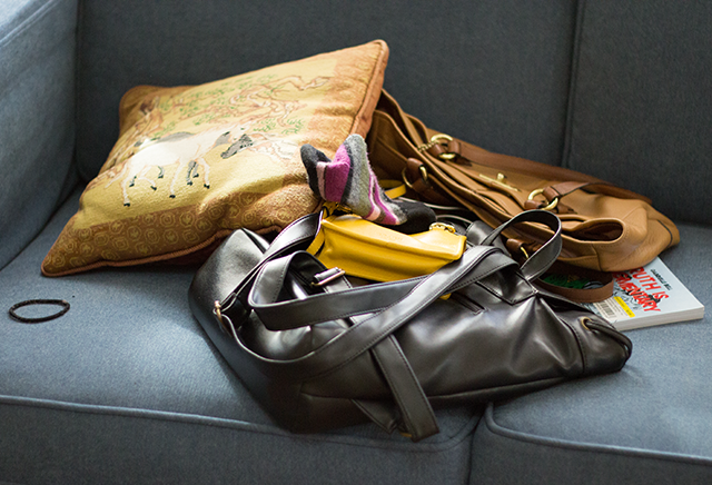 pile of purses on blue couch