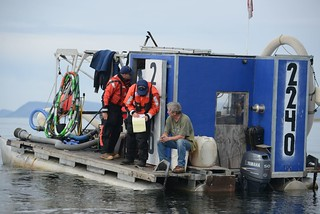 Petty Officer 1st Class Pete Harwell and Petty Officer 2nd Class Sean Purcell, both maritime enforcement specialists with Coast Guard Sector Anchorage, conduct a law enforcement boarding aboard a gold dredge vessel near Nome, Alaska, Aug. 3, 2014. Boardings are conducted to ensure that vessel crews are operating safely and complying with environmental regulations. U.S. Coast Guard photo by Petty Officer 2nd Class Grant DeVuyst.