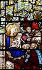 IV. Adoration of the Shepherds: One holds a lamb, one plays pipes. A third appears to offer a fleece.
