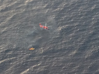A Coast Guard Dolphin helicopter from Air Station Traverse City, Mich., prepares to rescue three kayakers from Whaleback Shoal in Green Bay, July 11, 2014. The U.S. Coast Guard, along with the Royal Canadian Air Force and several local agencies assisted in the search and rescue of three kayakers reported missing on July 10, 2014. U. S. Coast Guard photo courtesy of the Royal Canadian Air Force