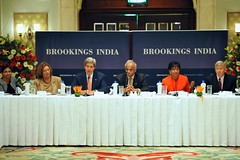 U.S. Secretary of State John Kerry, flanked by U.S. Commerce Secretary Penny Pritzker and Brookings India Chairman Vikram Mehta, addresses a group of U.S. and Indian business executives during a luncheon amid a Strategic & Economic Dialogue between the two countries in New Delhi, India, on July 31, 2014. [State Department photo/ Public Domain]