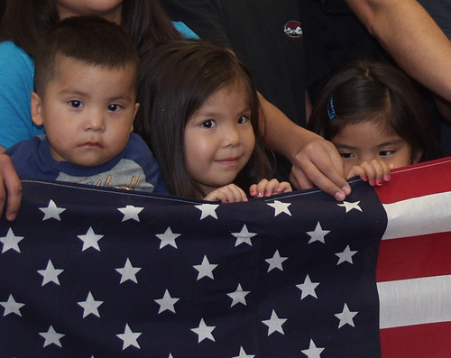 Reyanna Nastarcio's grandchildren hold the American flag that was presented to her by Rural Development Housing Administrator Tony Hernandez and State Director Terry Brunner.