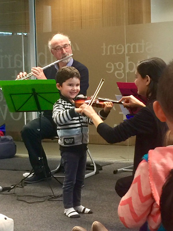 Child tries out the violin, Upper RIccarton Library