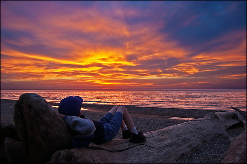 A youngster relaxes on a piece of driftwood, watching the beautiful sunset over Lake Michigan. Photo by Tom Gill.