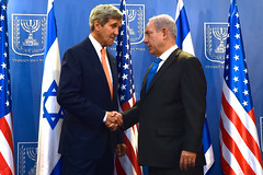U.S. Secretary of State John Kerry shakes hands with Israeli Prime Minister Benjamin Netanyahu in Tel Aviv, Israel, on July 23, 2014, before the two sat down to discuss a possible cease-fire to stop Israel's fight with Hamas in the Gaza Strip. [State Department photo/ Public Domain]