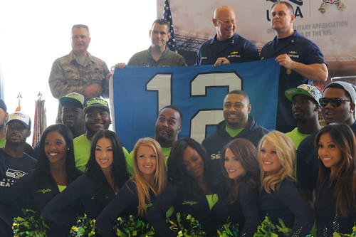 Master Chief Petty Officer Charles Lindsey (top right), command master chief of the Coast Guard 13th District, and Rear Adm. Richard Gromlich, commander of the Coast Guard 13th District, accept a Seattle Seahawks 12th Man flag from the Air Force 446th Airlift Wing during a ceremony held at Joint Base Lewis-McChord, Wash., Sept. 9, 2014. The Seattle Seahawks organization adopts a local military unit each year to show appreciation for the service members' dedication to their country and the team. (U.S. Coast Guard photo by Petty Officer 3rd Class Katelyn Shearer)