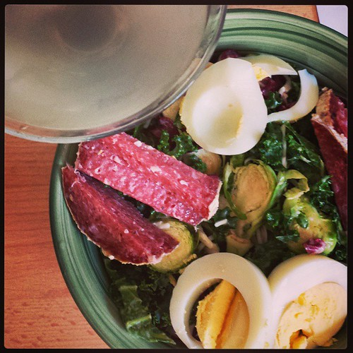 "Power lunch: kale salad with hard-boiled egg and good salami, coconut water ""martini"" #summer #food #health #100saladsummer"