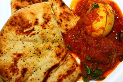 Egg and potato curry served with nan and garnished…