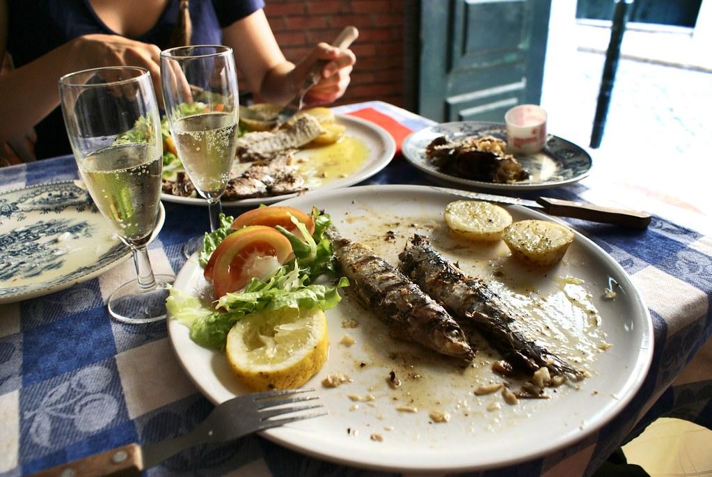 Sardines grillées, pomme de terre et salades avec un verre de vin verre légèrement pétillant = Le bonheur simple à Lisbonne.