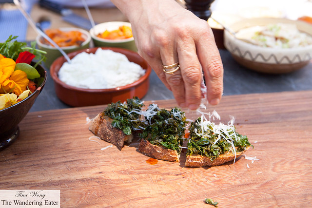 Chef Mona Talbott sprinkling pecorino on top of the spicy kale bruschetta