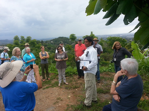 Ray Rodriguez, a collaborator from Para la Naturaleza, talks about the rural-urban ecotone and positive outcomes of community action as participants enjoy a birds-eye view overlooking the Río Piedras River Watershed boundaries in the San Juan metropolitan area, the final stop of an urban field trip on May 20 held as part of the Institute's 75th anniversary celebration. (U.S. Forest Service)