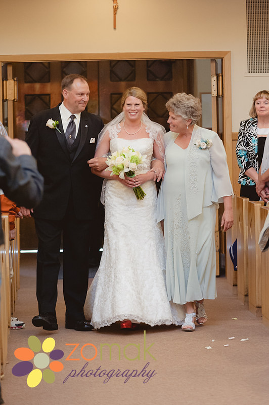 mother and father accompany bride down the aisle