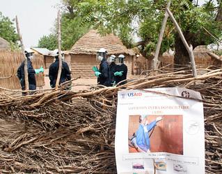 Spray operators in Keur Moussa, Senegal, in front of IRS poster
