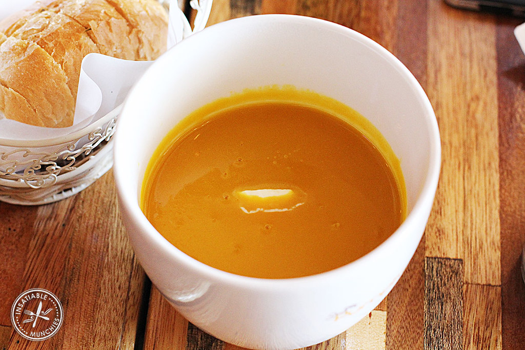 Pumpkin soup is served with a thick dollop of cream, and an aromatic basket of fluffy garlic bread