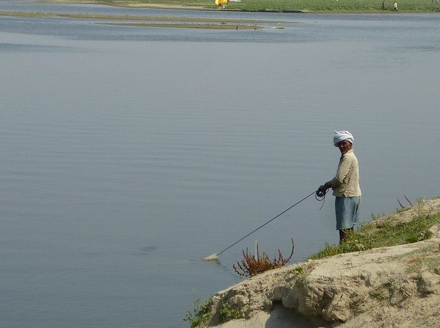 A fisherman casts a net into the river