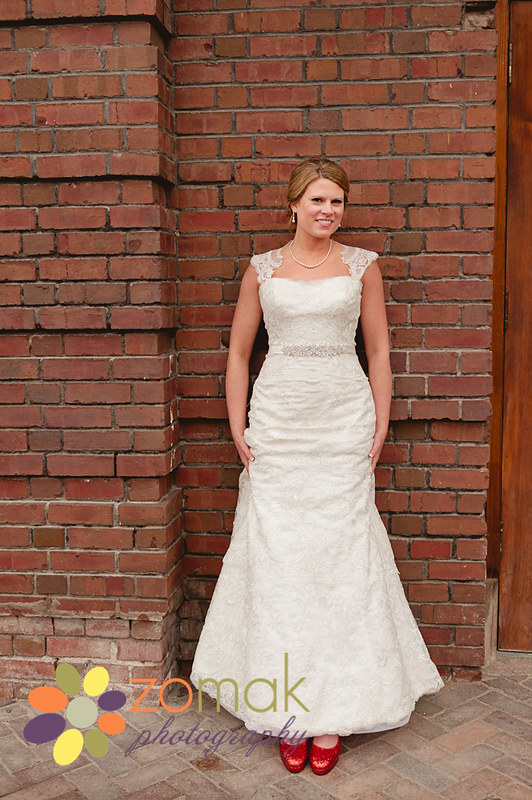 bride poses for portrait at front street station in front of brick facade