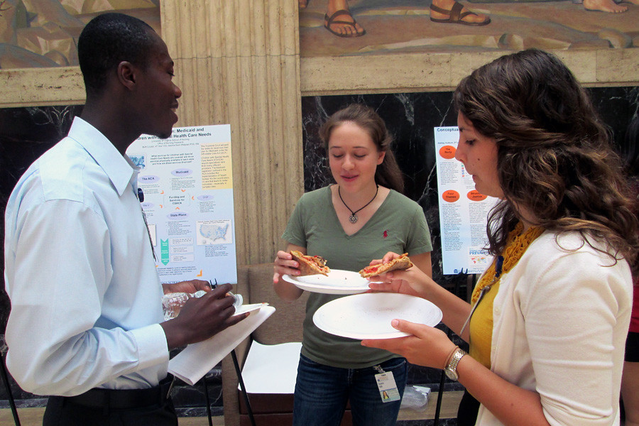 July 22, 2014 - Undergraduates munch on pizza and check out each other's research projects in the Clark Hall Mural Room.