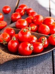 red juicy tomatoes cherry in brown wooden plate