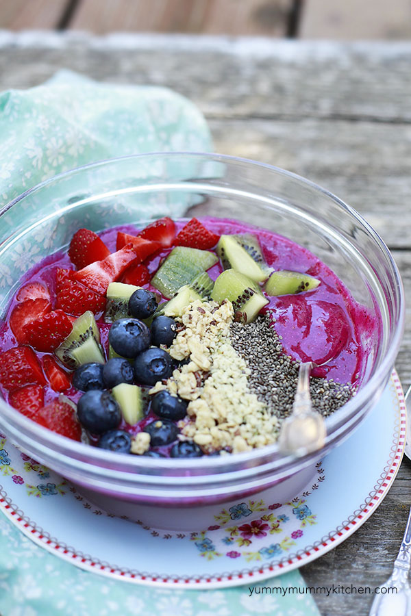 A beautiful pink dragon fruit smoothie bowl topped with berries, kiwi, granola, and chia seeds.