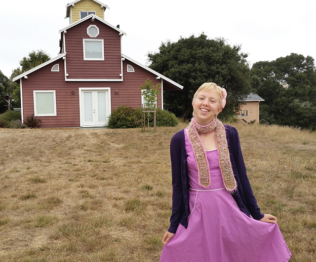 wearing a pinky-purple dress in front of a barn