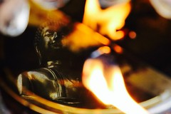 The Buddha reflected in a butter lamp in Chiang Mai, Thailand