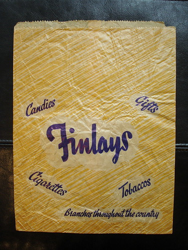 """A small paper bag with a yellowish striped background and dark blue text in a cursive font: """"Finlays / Candies / Gifts / Cigarettes / Tobaccos [sic] / Branches throughout the country""""."""