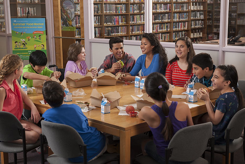 A group of young people at an indoor summer site enjoy a nutritious meal. They know that Summer Food Rocks!