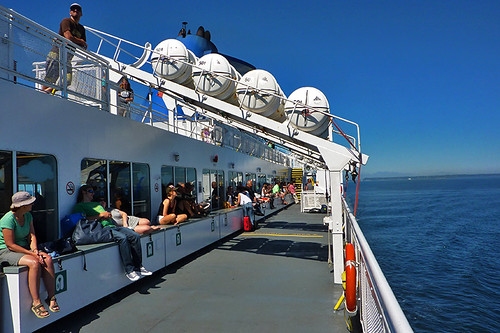 Passengers relax in the sunshine on the BC Ferry between Tsawwassen Ferry Terminal (Vancouver) and Swartz Bay (Victoria), British Columbia