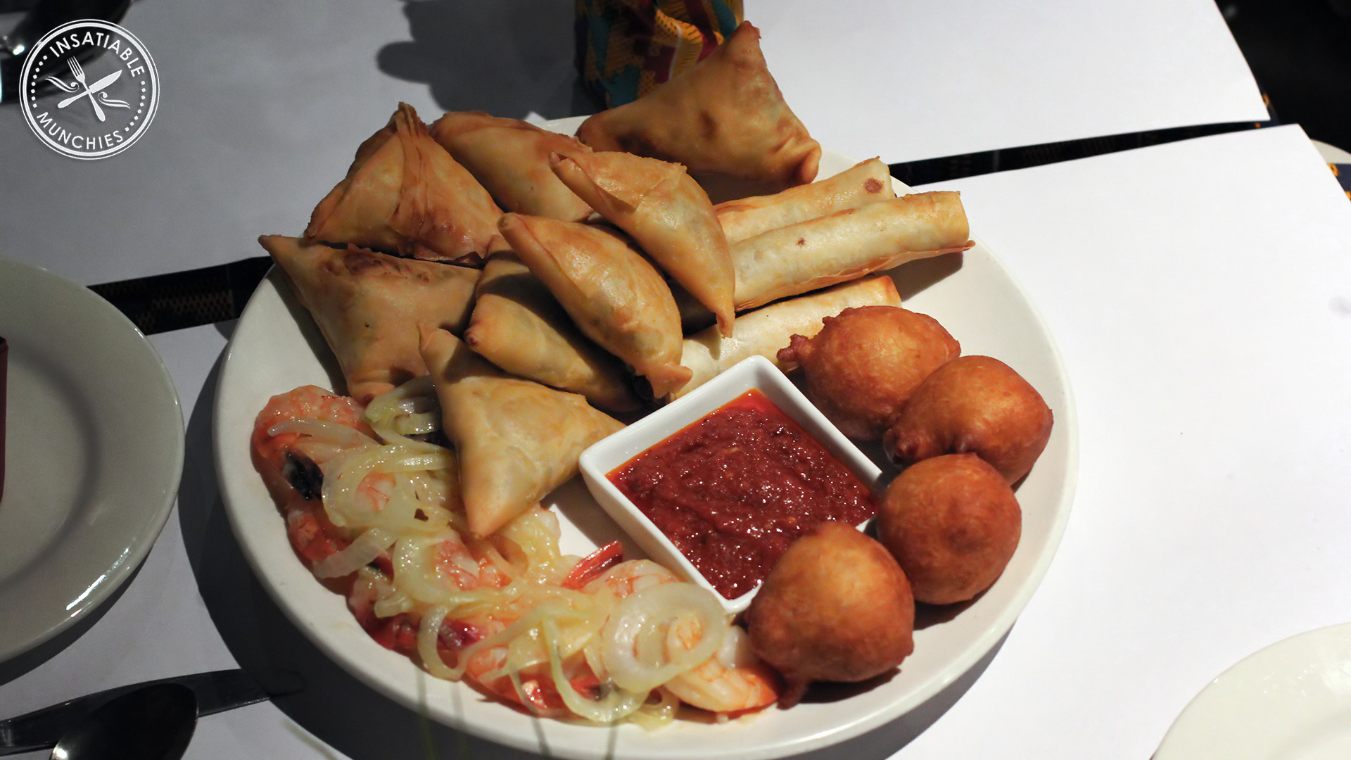African entree platter, including Vegetable Triangles, Mince Samosas, African Cigars, Kpoff Kpoff (dumplings), and Prawn Onion, with a tomato based dipping sauce.