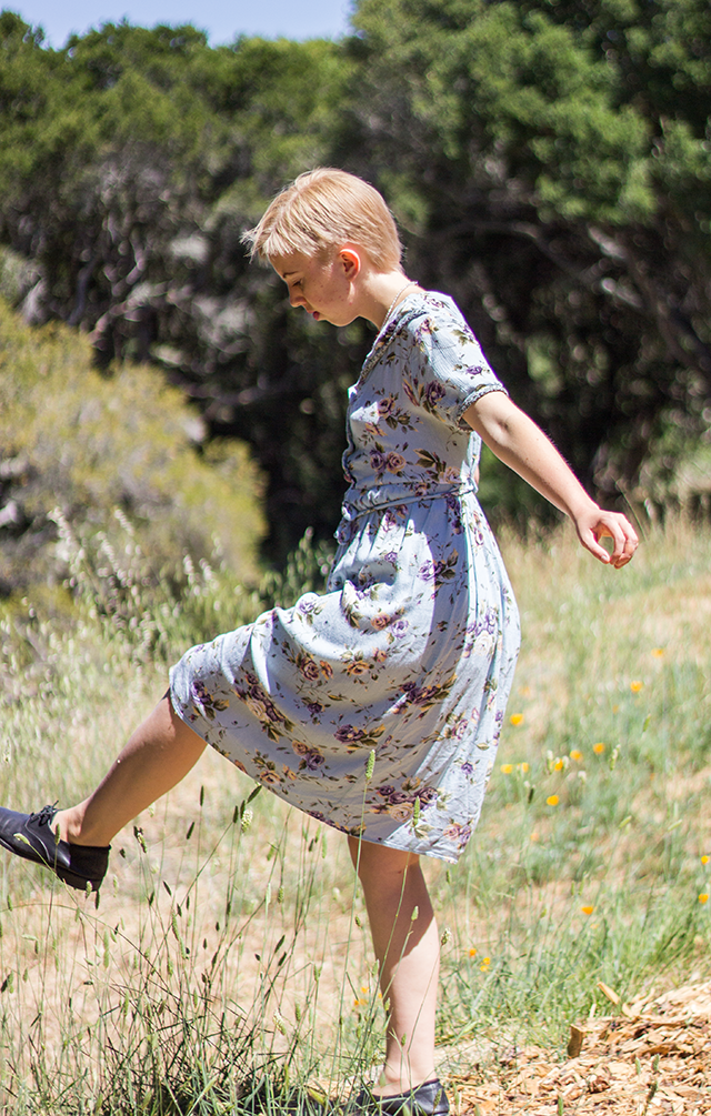 kicking the grass, floral mint dress, short blonde pixie cut