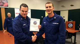 Coast Guard Lt. Richard Russell from the North Pacific Regional Fisheries Training Center in Kodiak, Alaska, presents Petty Officer 1st Class Brandon Hayward, of the Cutter Alex Haley, with an award for Stellar Student of the Boarding Officer Course June 12, 2014. The Alex Haley's crew completed training on fisheries regulations, living marine resource protection and commercial fishing vessel safety regulations at the NPRFTC during the week of June 9-13.  U.S. Coast Guard photo by Petty Officer 3rd Class Dale Arnould.