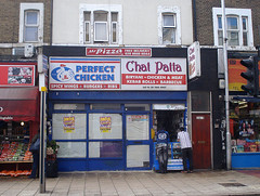 "A terraced shopfront with signs above reading ""Mr Pizza / Free Delivery / 020 8680 8844"", ""Perfect Chicken / Spicy Wings / Burgers / Ribs"", and ""Chat Patta / Biryani / Chicken & Meat / Kebab Rolls / Barbecue / Eat In Or Take Away"".  The fully-glazed frontage is covered in sheets of paper, and a couple of posters advertising a ""Fun Fair"" have been stuck up over this.  A kiosk selling mobile phone accessories is set into the right-hand side of the shop, and two people are leaning into it."