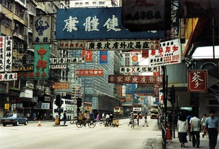 Signs and double deck buses, high rises, crossing - people walking, running, with bikes, a street, 1990 - the last decade of Colonial Hong Kong, soon to be returned to China