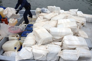 A U.S. Coast Guard crew member unloads a bale of marijuana from a panga boat that was seized 160 miles southwest of San Diego June 28, 2014. The Coast Guard detained three suspects and seized approximately 7,600 pounds of marijuana. (U.S. Coast Guard photo by Petty Officer 1st Class Henry G. Dunphy)