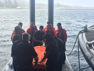 A Coast Guard Station Neah Bay 47-foot Motor Life Boat crew assists local emergency medical services personnel with the diver recovered near Cape Flattery, Washington, Aug. 19, 2014. The diver was transported to Neah Bay hospital for further medical evaluation and was reported to be in good condition. U.S. Coast Guard photo by Station Neah Bay.