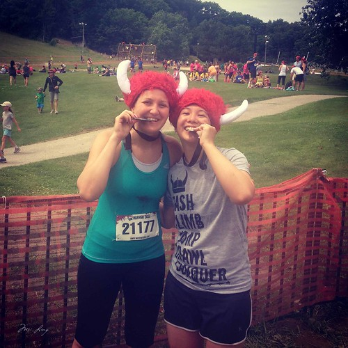 Mei and Nicola in red fuzzy warrior dash viking helmets biting into their medals.