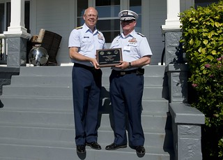 Rear Adm. Richard Gromlich, commander of the 13th Coast Guard District, presents Dean Wimer, commodore of the 13th Coast Guard District Auxiliary, a plaque to honor the Coast Guard Auxiliary for 75 years of volunteer service in keeping America's waterways safe, June 21, 2014. The Auxiliary was established by an act of Congress on June23, 1939, and has since then assisted the Coast Guard in all missions, with the exception of law enforcement activities. U.S. Coast Guard photo by Petty Officer 3rd Class Jordan Aki