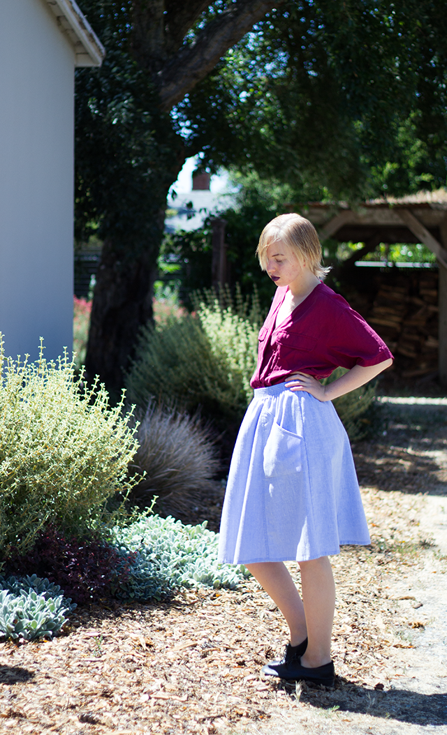 dark purple lipstick, billowy plum/magenta silk blouse, sky blue midi skirt with pockets