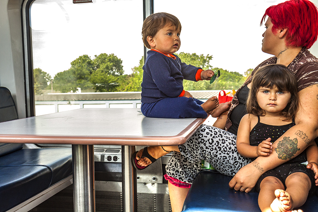 Woman-with-bright-red-hair-and-her-two-kids-in-train's-lounge-car--Wisconsin