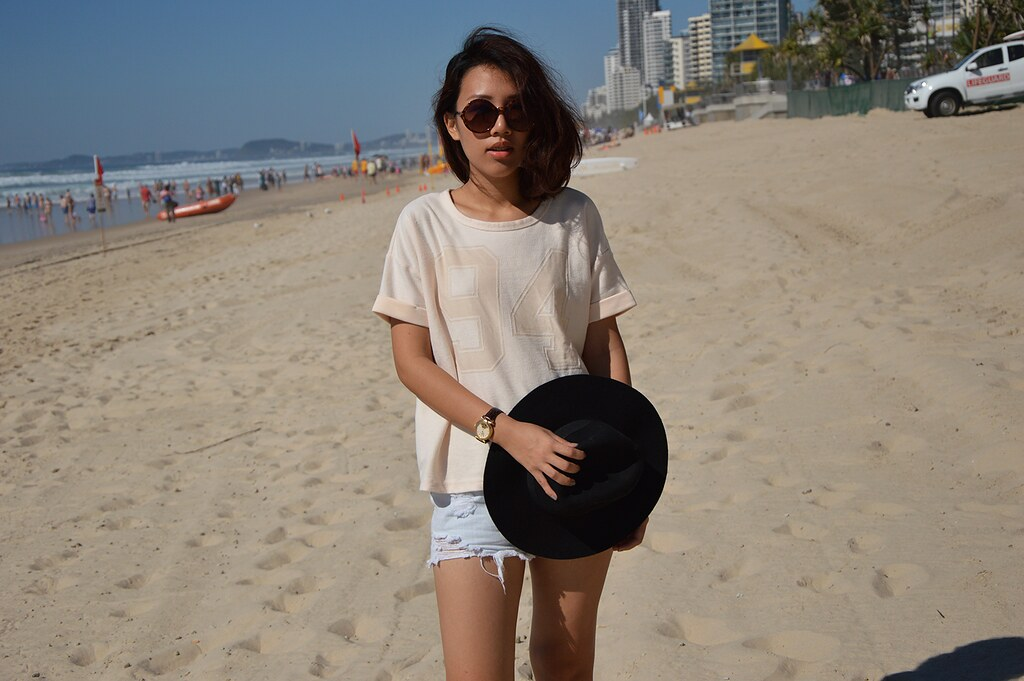 sporty shirts tops, ripped denim shorts, round tortoiseshell sunglasses