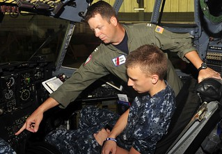 Lt. Sean Lott, a pilot at Coast Guard Air Station Clearwater, Fla., explains the controls of a HC-130 Hercules aircraft to Gray Wilson, a U.S. Navy Sea Cadet at the air station, Monday, June 9, 2014. During a week long internship, the sea cadets and Pinellas Park High School's First Responders Program learned about the Coast Guard's aviation assets and toured the air station. U.S. Coast Guard photo by Seaman Meredith Manning