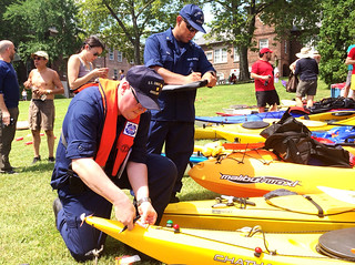 Coast Guard Auxiliarists Mike Kessler and Orlando Villa perform complimentary vessel safety checks during The Metropolitan Water Association's City of Water Day Festival on Governors Island, July 12, 2014. The event is a free day-long celebration that draws thousands of people from throughout the tri-state metropolitan region to participate in educational waterfront activities. (U.S. Coast Guard photo by Petty Officer 3rd Class Michael Himes)
